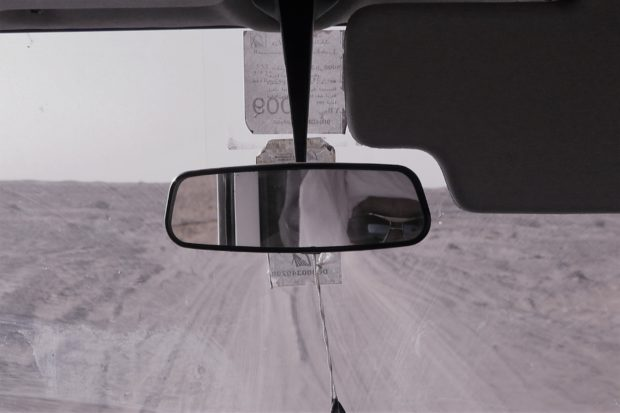 Photo of berber checking rearview mirror in the Sahara, Morocco